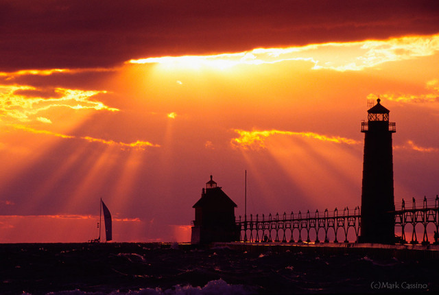 Sailboat in the sunset behind the Grand Haven, Michigan lighthouse.