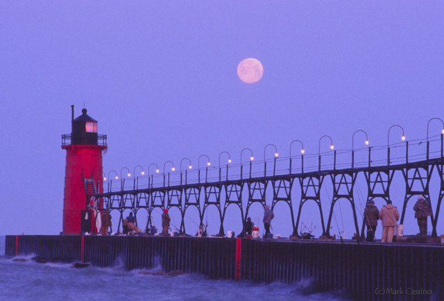 Fishermen looking at the setting full moon on the South Haven, Michigan pier.