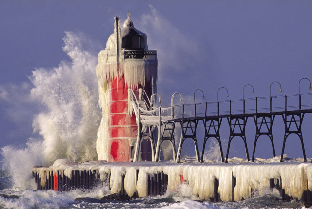 An icy wave breaks on the lighthouse at South Haven Michigan during a winter squall.